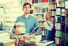 Uomo con il mucchio del libro nel deposito di libro Immagine Stock Libera da Diritti