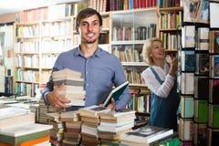 Uomo con il mucchio del libro nel deposito di libro Immagini Stock Libere da Diritti