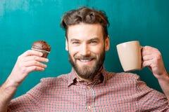 Uomo con il muffin ed il caffè immagini stock