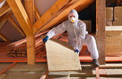 Uomo con il pannello di lana di roccia che installa strato dell'isolamento Fotografie Stock