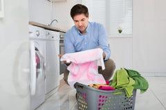 Uomo con il panno macchiato tenuta del canestro di lavanderia Immagine Stock Libera da Diritti