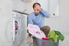 Uomo con il panno macchiato tenuta del canestro di lavanderia Fotografie Stock Libere da Diritti