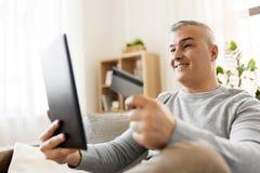 Uomo con il pc della compressa e carta di credito che comperano online Fotografia Stock