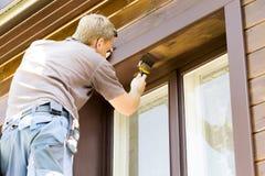 Uomo con il pennello che dipinge esterno di legno della casa fotografia stock
