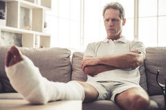Uomo con il piedino rotto Immagini Stock