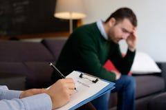 Uomo con il problema sanitario di salute mentale nello studio dello psichiatra fotografie stock