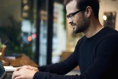 Uomo con il progetto di funzionamento del telefono cellulare che si siede nello spazio coworking facendo uso del computer portati Fotografia Stock