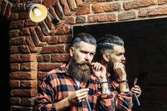 Uomo con il rasoio vicino allo specchio Immagine Stock