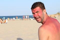 Uomo con il rossore che grida alla spiaggia fotografia stock