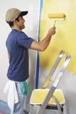 Uomo con il rullo che applica pittura gialla su una parete fotografia stock