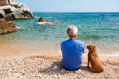Uomo con il suo cane alla spiaggia Fotografie Stock