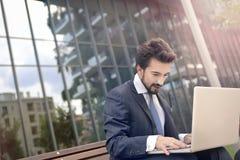 Uomo con il suo computer portatile Immagine Stock