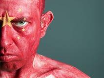 Uomo con il suo fronte verniciato con la bandierina della Cina Fotografie Stock Libere da Diritti