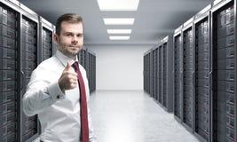Uomo con il suo pollice giusto su nella stanza del server per archiviazione di dati, pro Immagini Stock Libere da Diritti