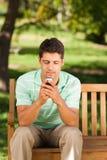 Uomo con il suo telefono sul banco Immagine Stock