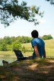 Uomo con il taccuino sul riverbank fotografia stock libera da diritti