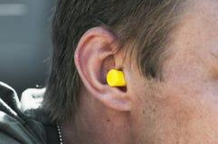 Uomo con il tappo per le orecchie giallo in suo orecchio fotografia stock