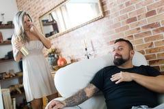 Uomo con il tatuaggio che si siede nella poltrona e nella donna che mangiano bottiglia dorata di champagne nel fondo fotografie stock