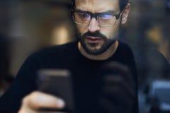 Uomo con il telefono cellulare che riceve messaggio dal servizio bancario con le fatture ed i rapporti delle spese facendo uso de Fotografie Stock