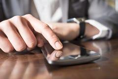 Uomo con il telefono cellulare collegato ad uno smartwatch Mani del primo piano Fotografia Stock
