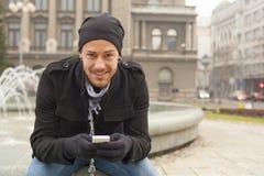 Uomo con il telefono cellulare ed il cappello in città, spazio urbano Fotografia Stock