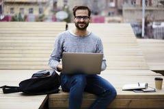 Uomo con il telefono cellulare facendo uso di collegamento senza fili ad Internet ed il computer portatile nella zona di wifi Immagini Stock