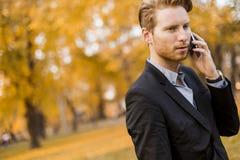 Uomo con il telefono cellulare nel parco di autunno Fotografie Stock
