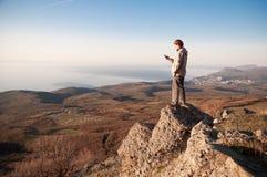 Uomo con il telefono cellulare sulla cima del mondo Immagine Stock