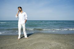 Uomo con il telefono mobile alla spiaggia Fotografie Stock