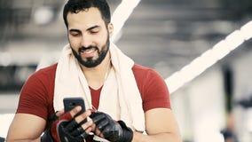 Uomo con il telefono in palestra video d archivio