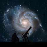 Uomo con il telescopio che esamina le stelle Galassia della girandola Fotografie Stock Libere da Diritti
