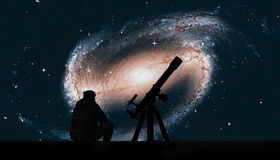 Uomo con il telescopio che esamina le stelle Galassia a spirale immagine stock libera da diritti