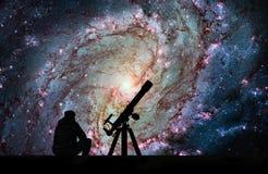 Uomo con il telescopio che esamina le stelle 83 più sudici, pi del sud Immagine Stock