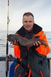 Uomo con il trofeo di pesca del lupo di mare Immagini Stock Libere da Diritti