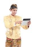 Uomo con il vestito tradizionale di Java facendo uso del PC della compressa immagine stock libera da diritti
