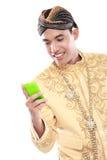 Uomo con il vestito tradizionale di Java facendo uso del telefono cellulare immagini stock libere da diritti