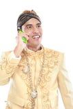 Uomo con il vestito tradizionale di Java facendo uso del telefono cellulare fotografia stock