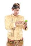 Uomo con il vestito tradizionale di Java facendo uso del telefono cellulare Fotografie Stock