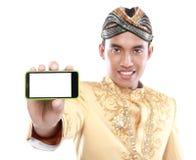 Uomo con il vestito tradizionale di Java facendo uso del telefono cellulare fotografia stock libera da diritti