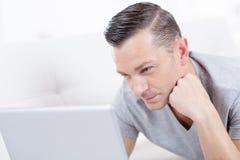 Uomo con il web praticante il surfing del computer portatile a casa Fotografia Stock