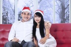 Uomo con l'abbraccio del cappello di Santa la sua amica Fotografie Stock Libere da Diritti