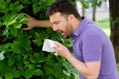 Uomo con l'allergia o il ill con il naso di starnuto e di pulizia del raffreddore da fieno Immagini Stock