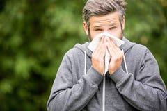 Uomo con l'allergia o il ill con raffreddore da fieno Immagini Stock