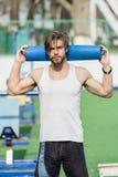 Uomo con l'ente muscolare, l'yoga della tenuta della barba o la stuoia di forma fisica Immagini Stock Libere da Diritti