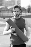 Uomo con l'ente muscolare, l'yoga della tenuta della barba o la stuoia di forma fisica Immagini Stock