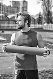 Uomo con l'ente muscolare, l'yoga della tenuta della barba o la stuoia di forma fisica Fotografia Stock