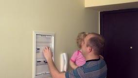 Uomo con l'interruttore elettrico del controllo della neonata nella sala 4K video d archivio