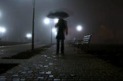 Uomo con l'ombrello che cammina nel parco di notte Immagini Stock Libere da Diritti