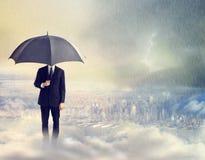 Uomo con l'ombrello sopra la città Immagine Stock