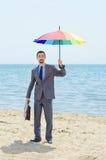 Uomo con l'ombrello sulla spiaggia fotografia stock libera da diritti